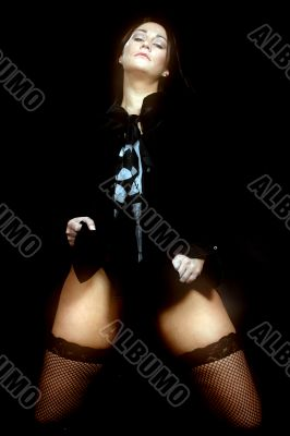 a woman in stockings against a black background