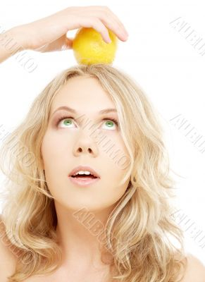 healthy blond holding lemon on her head