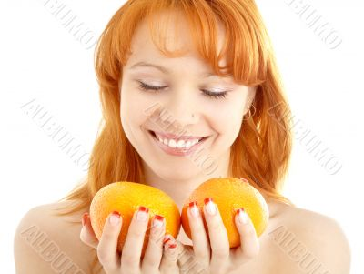 cheerful redhead holding two oranges over white