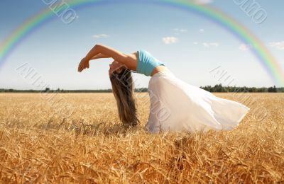 stretching woman in the meadow with rainbow