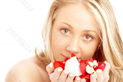 happy blond in spa with red and white petals