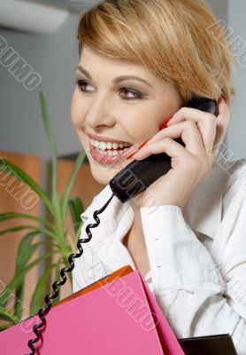 office lady with folders making a phone call