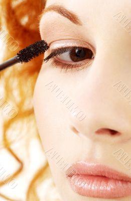 lovely redhead applying black mascara