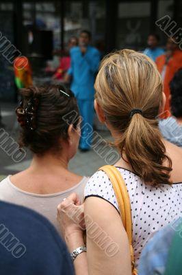 Two young women watching samba band