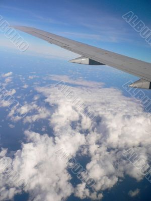 Aeroplane wing over clouds.