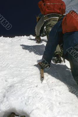 Climbers kicking steps up steep snow