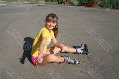Girl sits on the floor with roller blades