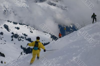 Yellow skier traversing steep slope