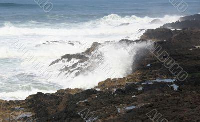 Surf breaking on volcanic rocks