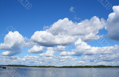 blue sky with curly white clouds above the lake