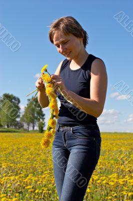 woman twining a dandelion wreath