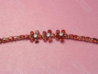 Jewelry bracelet with garnets on pink background