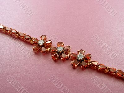 Jewelry bracelet with garnets on pink background