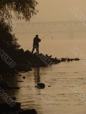 Silhuette of alone fisher near sunset river