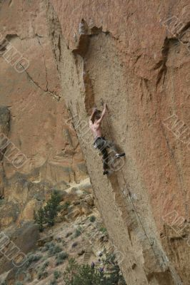 Climber on overhanging cliff