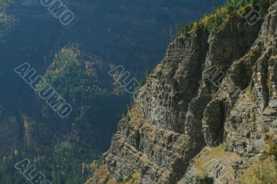 Steep layered cliff and forest valley