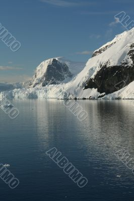 Mountains & glaciers reflected in calm ocean
