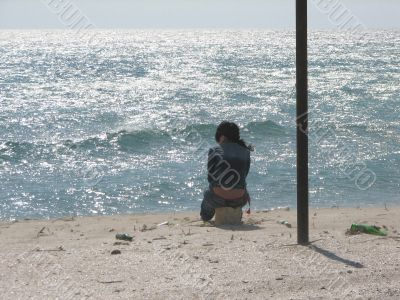 The girl in loneliness sits at sea coast