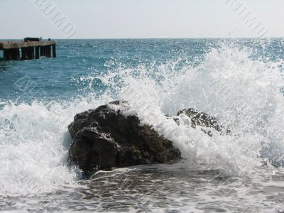 cold sea waves crashing against the coast stone