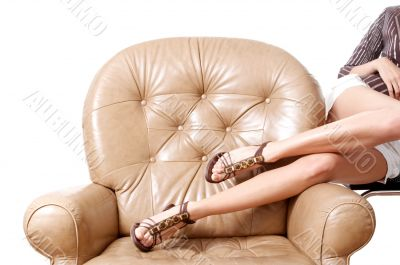 Woman`s beautiful long legs laying on the armchair