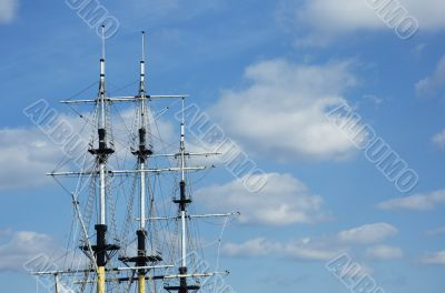 masts of frigate over blue sky with space for text