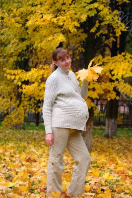 Pregnant woman in autumn park hold maple leaf #4