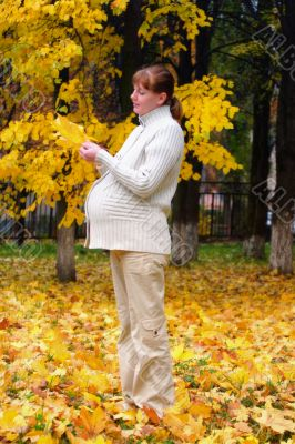Pregnant woman in autumn park hold maple leaf #1