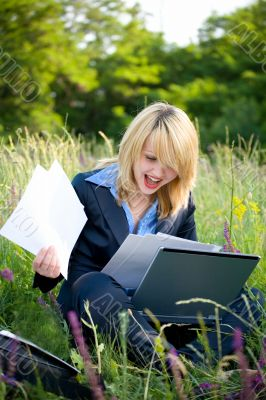 Happiness woman on grass with laptop and documents