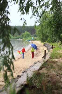 Mother and daughter with umbrella walking on riverside under rai