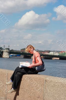 Girl reading magazine on canal border in Saint Petersburg