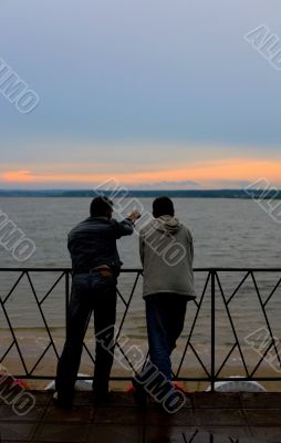Two men on a river bay look at sunset #1