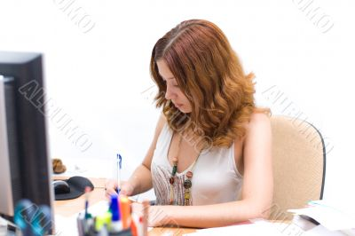 Attractive girl writing document in office