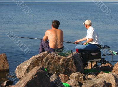 Seated men fishing off a shoreline