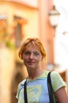 Pretty red-headed girl on street look at camera