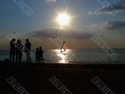 Silhouette of people looking at windsurf at sunset