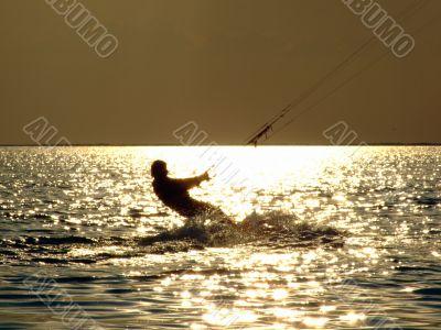 Silhouettes kitesurf on a gulf on a sunseet