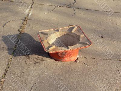 construction cone filling pothole in sidewalk