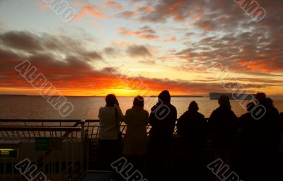 Cruise ship passengers taking pictures of sunset
