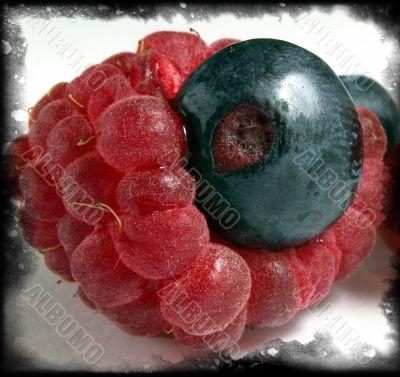 ripe raspberry with a bilberry inside