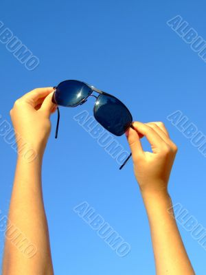 Female hands hold sunglasses