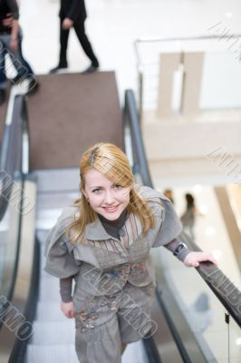 Pretty girl standing on escalator and moving up