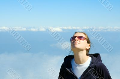 smiling girl looking in the blue cloudy sky with copyspace