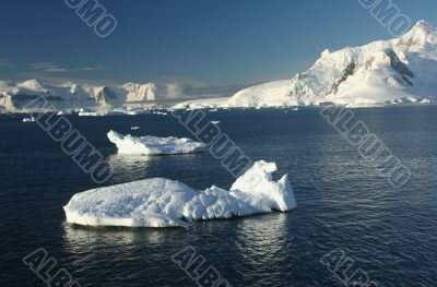 Icebergs, mountains, clear blue sky