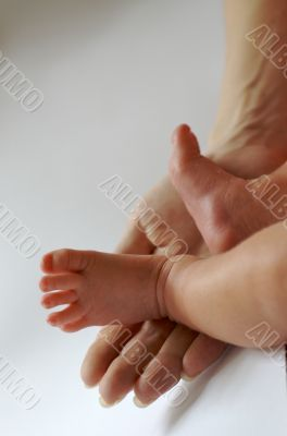 newborn`s feet on woman`s palm