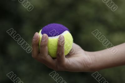 childs hand with tennis ball