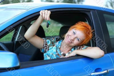 Young woman in a car with key