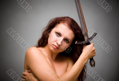 Attractive woman with sword on gray background