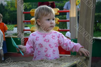 Toddler with shovel in sandbox