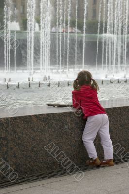 Thoughtful child near fountain