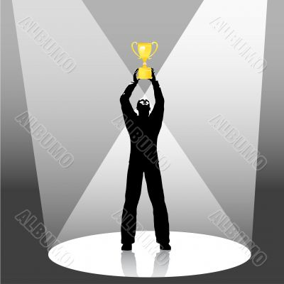 person holds trophy up in spotlight